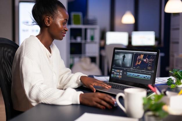 真夜中に営業所の机に座っているプロのラップトップで映画を編集する黒人の喜んでビデオグラファー