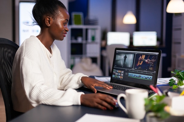 Black delighted videographer editing movie on professional laptop sitting at desk in business office at midnight