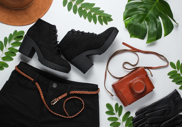 Black denim shorts with a leather belt, retro camera in cover, hat, boots, gloves on white background with green tropical leaves.