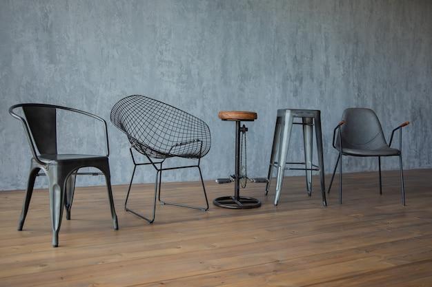 식물 회색 벽에 나무 바닥에 검은 디자이너 의자