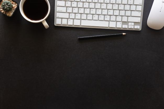 노트북, 스마트폰 및 기타 작업 용품이 있는 블랙 데스크 사무실과 커피 한 잔. 텍스트를 입력할 수 있는 복사 공간이 있는 상위 뷰입니다. 평면에 책상 테이블 필수 요소에 디자이너 작업 공간.