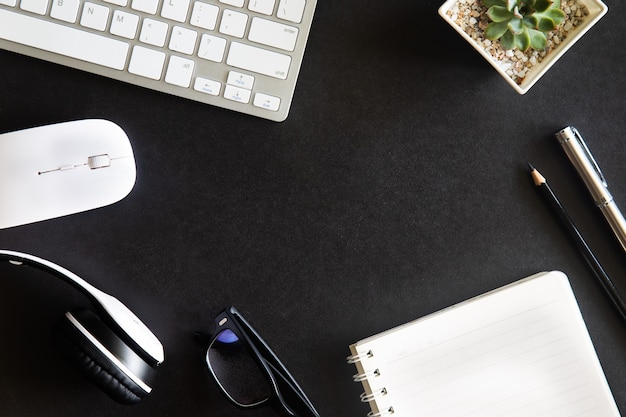 Black desk office with laptop, smartphone and other work supplies with cup of coffee. top view with copy space for input the text. designer workspace on desk table essential elements on flat lay.