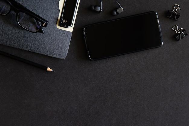스마트 폰, 이어폰, 클립 보드 및 안경이있는 블랙 데스크 오피스