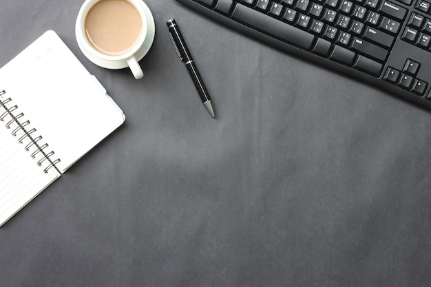 Black desk with coffee cup, keyboard, notebook,and pen placed in the office.