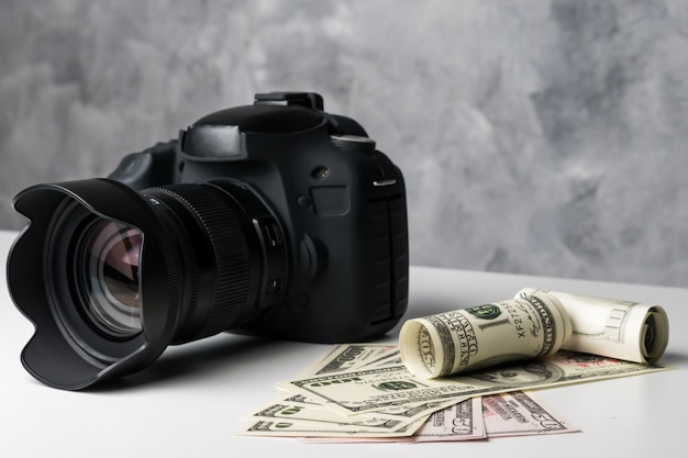 A black digital camera and banknotes on a white table with grunge background.