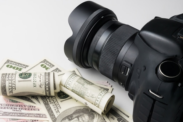 A black digital camera on banknotes with white background.