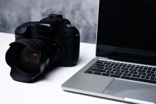 A black digital camera and a computer laptop on a table.