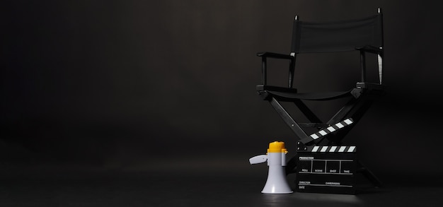 검은색 감독 의자와 클래퍼 보드 또는 검은 배경에 확성기가 있는 영화 클래퍼보드. 비디오 제작 또는 영화 영화 산업에서 사용