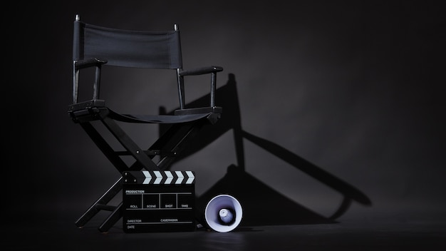Черный стул режиссера и доска с хлопушкой или фильм с 'хлопушкой' с мегафоном на черном фоне. использование в производстве видео или киноиндустрии