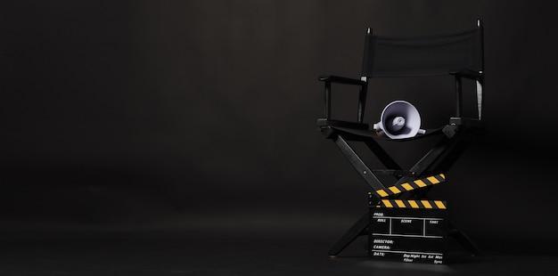 검은색 감독 의자 및 클래퍼 보드 또는 검은색 배경에 노란색 확성기가 있는 영화 클래퍼보드. 비디오 제작 또는 영화 영화 산업에서 사용