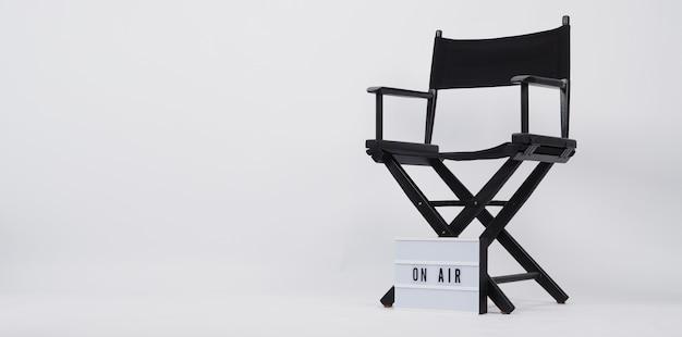 검은색 감독 의자와 단어가 있는 라이트박스. 흰색 배경의 비디오 제작, 영화 및 영화 산업에 사용됩니다.