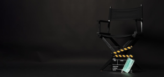 黒のディレクターズチェアと黄色のカチンコまたはスレート、黒の背景にフェイスマスクとメガホン。
