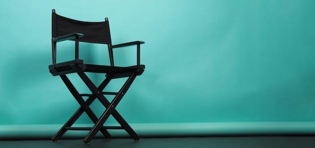 민트나 티파니 블루 배경에 검정 감독 의자가 분리되어 있거나 영화 클래퍼보드가 있습니다.