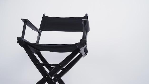 Черный режиссерский стул используется в производстве видео или кино и кино. он помещен на белый фон. .