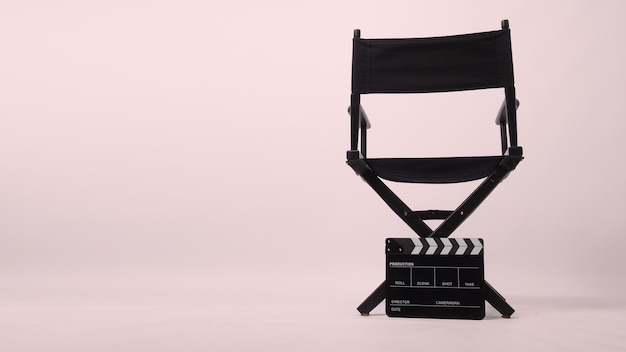 Black director chair with clapper board put on the ground on light pink background.