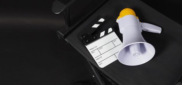클래퍼보드(clapperboard) 또는 영화 클래퍼 보드(clapper board)와 메가폰이 있는 black 감독 의자는 비디오 제작이나 영화 및 영화 산업에서 사용됩니다.