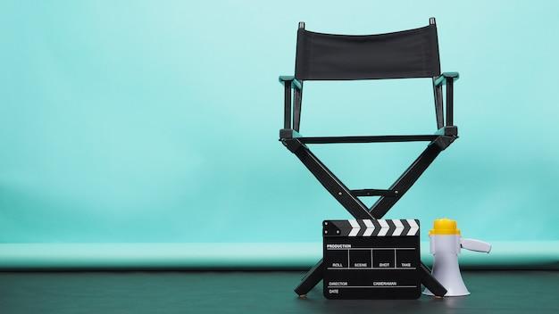 메가폰과 클래퍼보드가 있는 black 감독 의자 또는 녹색 또는 tiffany blue 및 검은색 바닥 배경에 영화 클래퍼 보드가 있습니다. 비디오 제작 또는 영화 및 영화 산업에서 사용합니다.