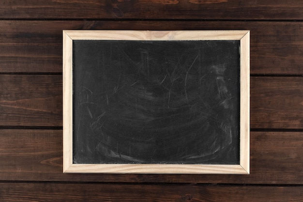 Black dirty chalkboard in a frame on a dark wooden background, copy space, top view