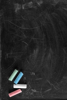 Black dirty chalkboard texture with different colors chalk pieces, copy space