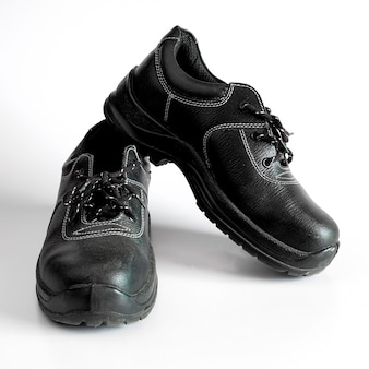 Black and dirty pair of children's shoes on background.