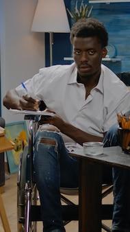 スタジオで現代の描画に取り組んでいる黒人障害者芸術家