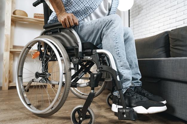 Черный инвалид садится на инвалидную коляску у себя дома