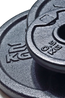 Black discs of a collapsible dumbbell with an inscription 2 kg. close-up.