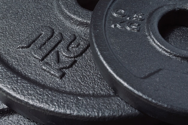Black discs of a collapsible dumbbell with an inscription 2 kg
