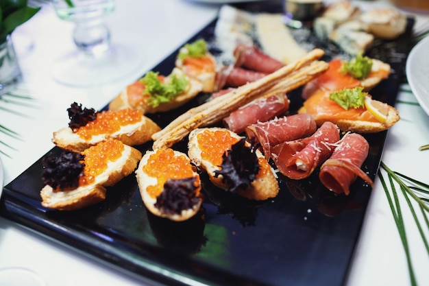 Black dish with snacks made of meat and caviar