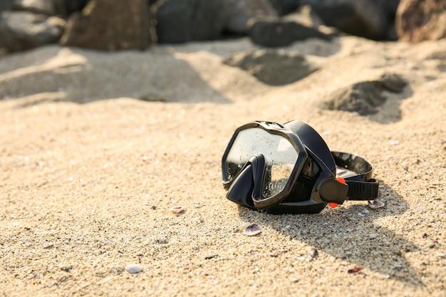 砂の上の黒いダイビングマスク