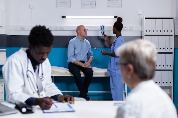 机に座っている年配の患者に相談する黒人医師
