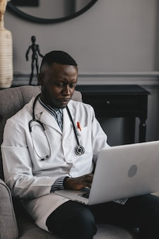Black doctor in a gray chair with a laptop remotely consults a patient. high quality photo
