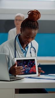 Black doctor holding virus animation on tablet
