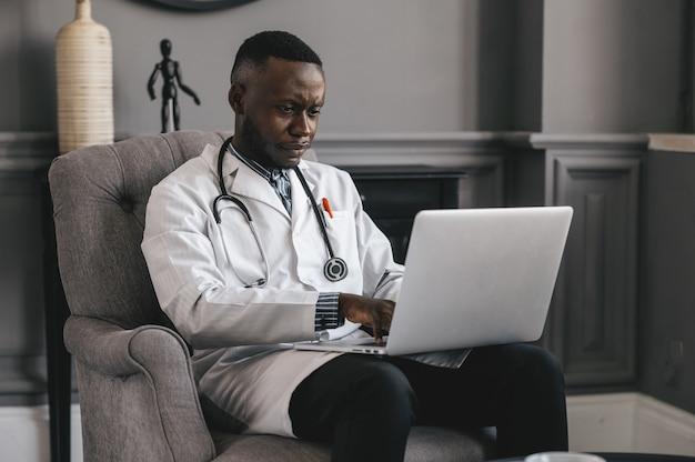 Черный доктор с помощью ноутбука, чтобы общаться с пациентом