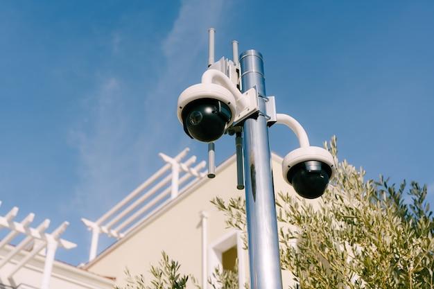 검은색 돔 모양의 무선 조종 감시 카메라는 배경에 있는 기둥에 있습니다.
