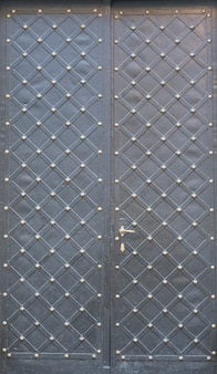 Black double metal doors with rhombic pattern and rivets.