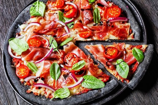 ハモンスライス、モッツァレラチーズ、トマト、ほうれん草の葉、赤玉ねぎと黒の生地のピザ、上からの木製テーブルの水平方向のビューの黒い大皿に