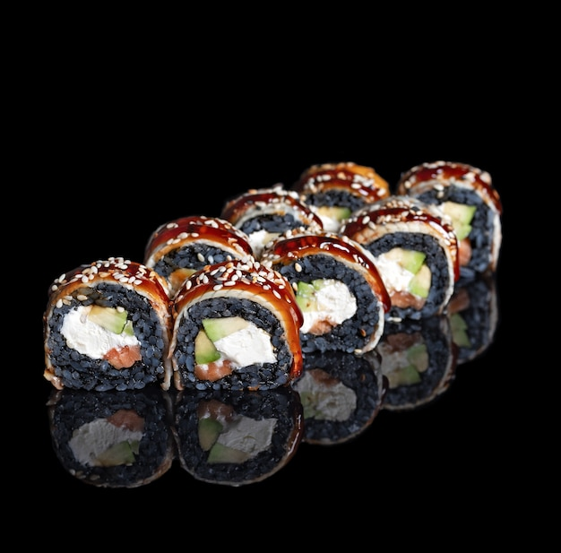 Black dragon sushi roll. sushi rolls with black rice, salmon, avocado with reflection on black background. copy space. close up. japanese cuisine. photo for menu