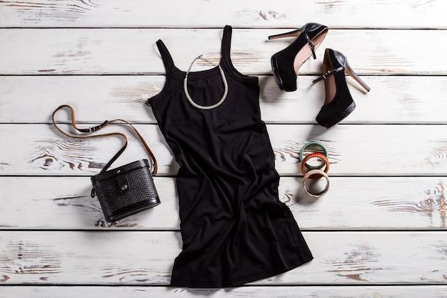 黒のドレス、靴、ジュエリー。テーブルの上の黒人女性の衣装。財布と華やかな暗い服。レトロな財布とモダンな服。