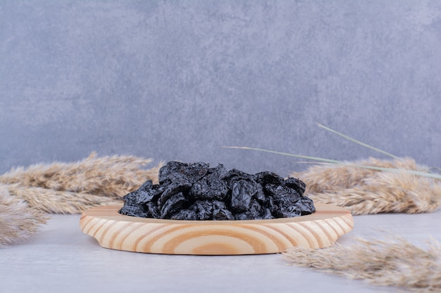Prugne secche nere isolate su un piatto di legno