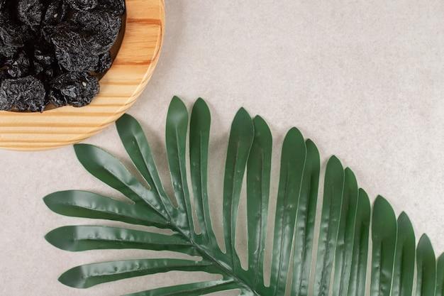 木製の大皿に黒のドライプラム。