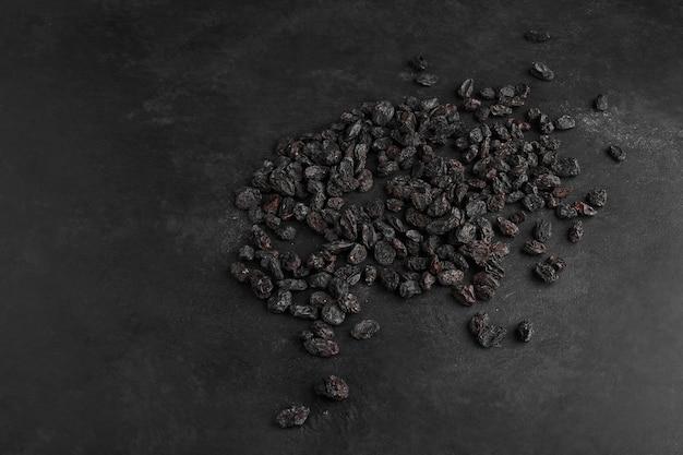 Black dry sultanas on black background.