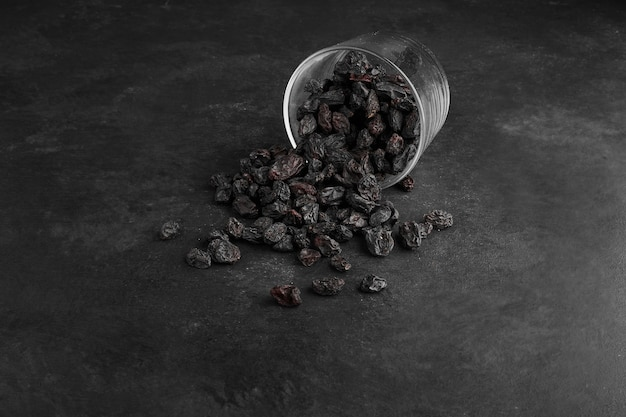 Black dry sultanas out of a glass cup on black surface.