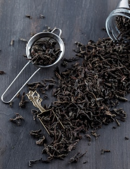Черный сухой чай в сите, опарнике, ветроуловителе на деревянном поверхностном взгляде высокого угла.