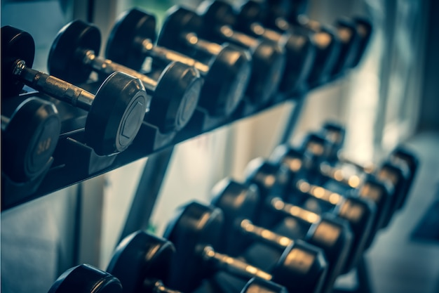 Black dumbbell set. close up many metal dumbbells on rack in sport fitness center