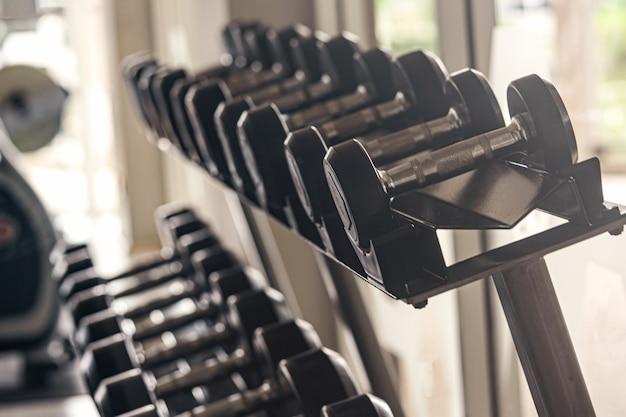 검은 아령 카운터에 체육관에서 설정합니다. 창에서 빛.