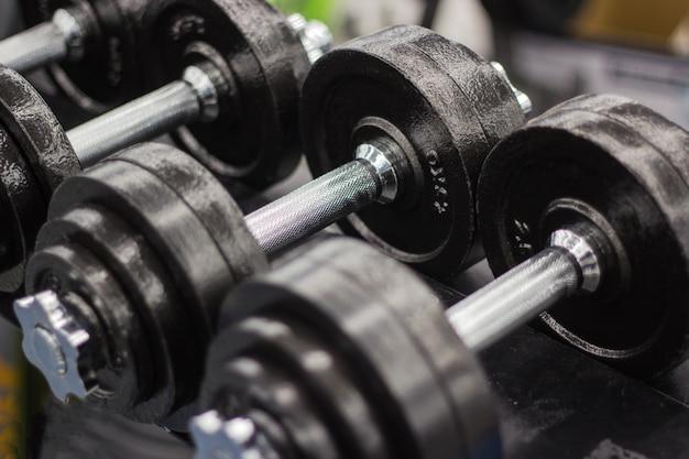 Black dumbbell set, many metal dumbbells on rack in sport fitness center