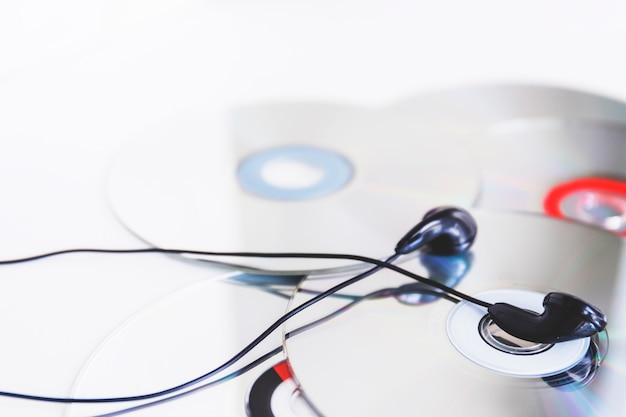 Black earphone on compact disc against white background