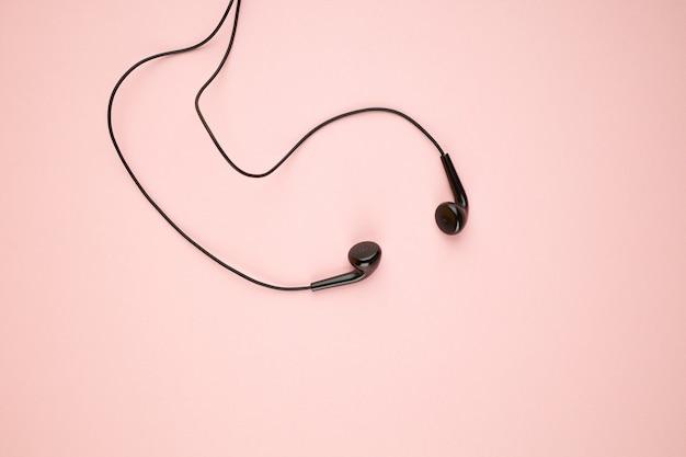 핑크 파스텔 배경에서 격리하는 블랙 이어폰. 평평한 평신도. 대기권 밖. 음악 미니멀리즘 개념
