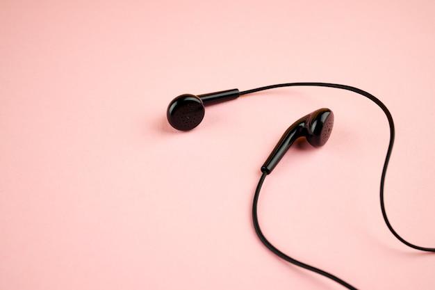 핑크 파스텔 배경에 검은 이어폰. 평평한 평신도. 대기권 밖. 음악 최소한의 개념